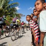 children watching riders in the Tour de Timor