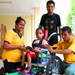 Photo of Timor-Leste team working with a child wheelchair user