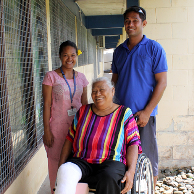 A woman using a wheelchair with a bandage around one leg smiles for a photo with two service providers who stand next to her.