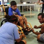 A child in Fiji being fitted with his new wheelchair.