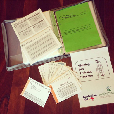 A photo of the Walking Aids Training Package ready to go to PNG, including a folder with training cards, posters and activity cards.