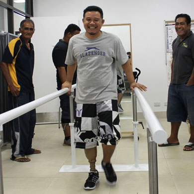 Samoan man walking with his new prostheses for the first time