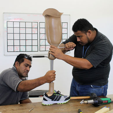 Two Samoan staff adjusting a the knee of a prostheses