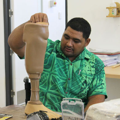 Samoan man holding a prosthetic leg