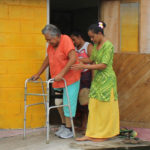A woman learning to use her prosthetic leg walking outside her house, supported by one of the MDS staff members.