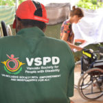 James Kalo faces away from camera with the VSPD logo showing. Motivation Australia staff member Claire is in the background examining a wheelchair