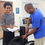 A male participant of the training adjusts a wheelchair, while a female participant checks off a list of changes that need to be made.