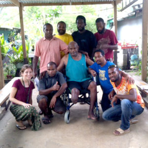A male wheelchair user is visited at home, and has taken a photo with the team of training participants and trainers that have visited him at home for a follow up appointment.