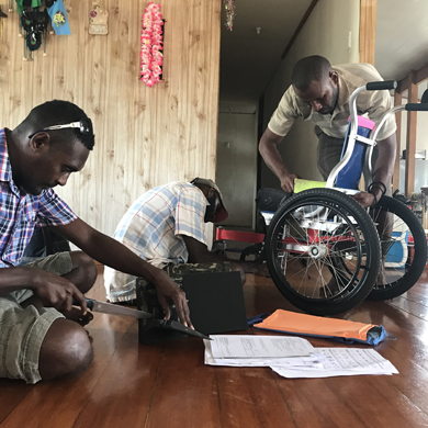 Three personnel work on a wheelchair in a clients home. One is measuring a cushion to cut, two are checking the nuts and bolts!