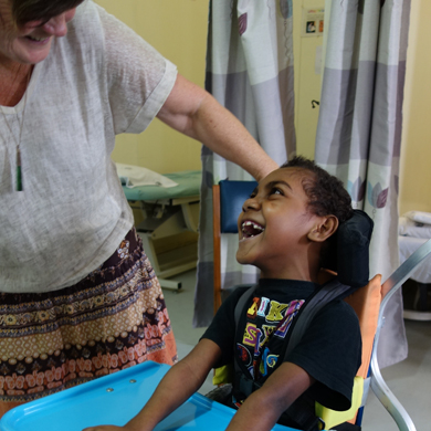 A young boy in his wheelchair is looking up and laughing at a woman standing next to him, looking at him and smiling.