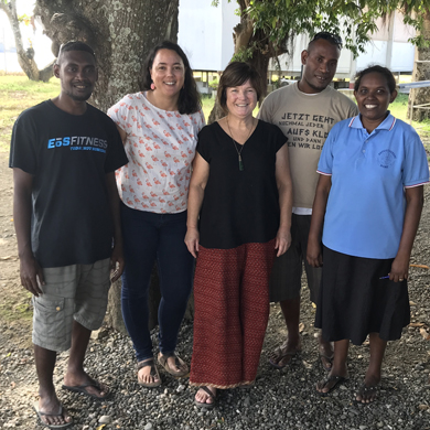 Five people stand under a large tree in the Solomon Islands. Two Solomon Island men, one Solomon Island woman and two Australians. They are standing in a team photo, and smiling.