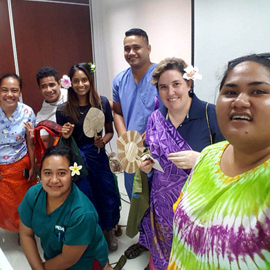 A group selfie shows 5 women and two men smiling at the camera. The nurses are wearing scrubs. Nalini and Katrina are holding gifts including lavalavas, fans, and flowers.