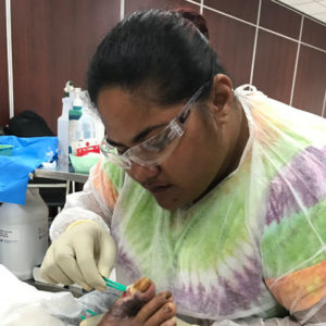 Image description: A nurse wearing safety glasses, a gown and gloves probes a toe ulcer with sterile forceps. Behind her we can see a dressing trolley