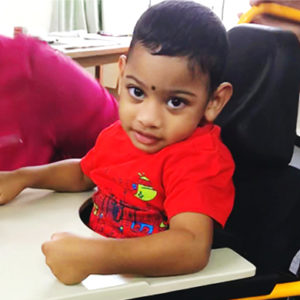 Fiji: A female child using a wheelchair looks at the camera. We can see the arm of his caregiver resting on his tray.
