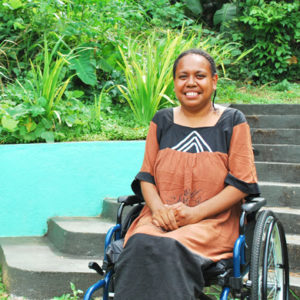 Ellen is sitting in her wheelchair smiling at the camera with her hands clasped on her lap. She is wearing a black and brown dress. Behind her are steps leading up to a garden of green shrubs and trees. To her right is a bright blue wall.