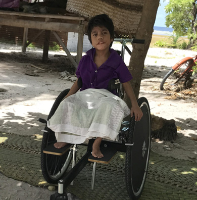 A child in her wheelchair, sitting in front of her Kiribati home - a traditional built house on stilts, on the beach.