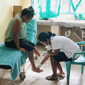 Kiribati: A female nurse performs a diabetic foot check up on a female patient in a clinical setting.