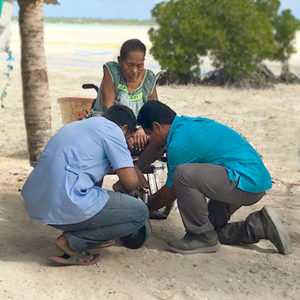 Kiribati: Two male clinicians/technicians are knelt down to assist an elderly woman using a wheelchair. We can see a stretch of beach in the background.