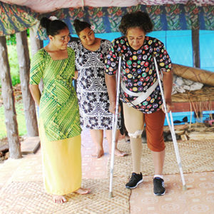 Samoa: Two female service providers in bright dresses watch as another woman with a prosthesis and crutches walks across the floor unassisted.