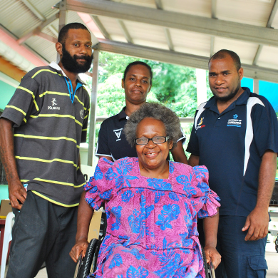 Vanuatu: A woman using a wheelchair smiles for the camera. Two men and a woman stand behind her, also smiling