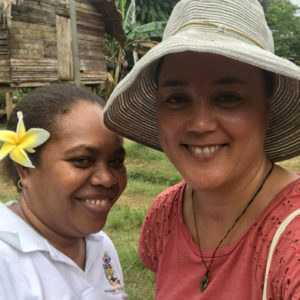 Two women take a selfie, one is from the Solomon Islands, and the other from New Zealand. In the background is a solomon island, hand-built local house.