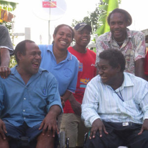 Group photo with two men sitting in wheelchairs, looking at each other and laughing. Behind them are two men and a woman, looking at the camera an laughing. All of them are from the Solomon Islands.