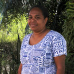 Profile photo of Elsie Taloafiri from the Solomon Islands, wearing a blue and white patterned dress. She is standing in front of tropical trees.