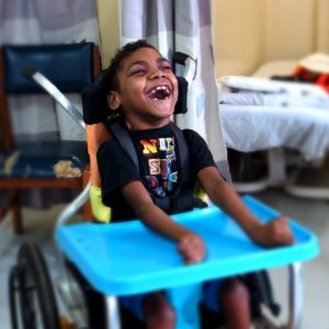 A Solomon Islands boy sits in his new wheelchair for kids wheelchair. He is laughing and his head is tilted back as he looks at his family (who are out of the shot). he is in a clinical setting.