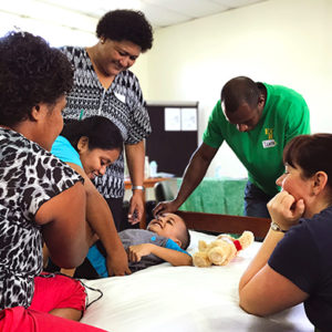Fiji: A group of five adults watch and assist a male child with his physical therapy. The child is lying on a bed with a teddy bear next to him. All are smiling.