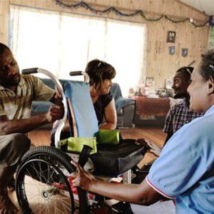 Solomon Islands: A group of four adults collaborate to maintain a wheelchair intended for a child during a home visit.