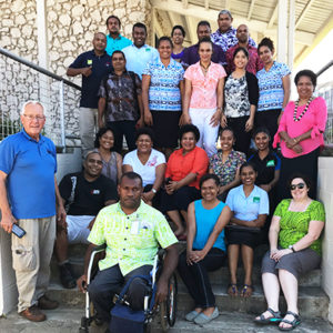 Fiji: A group of 23 people smile for the camera. One man at the front is a wheelchair user. Another man in the back gives a thumbs up. All are wearing bright, colourful shirts.