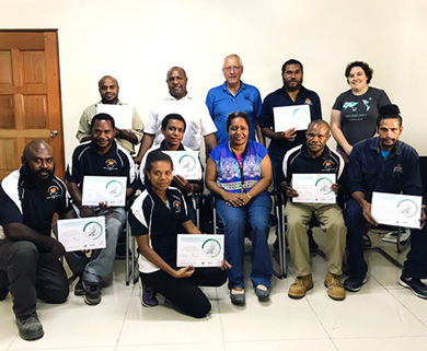 Three Papua New Guinean women, seven Papua New Guinean men, an Australian and an American are posed for a photo inside a beige room. Five are seated with five standing behind and two squatting in front. The eight training participants are dressed in their navy blue or khaki service uniforms and are holding certificates.