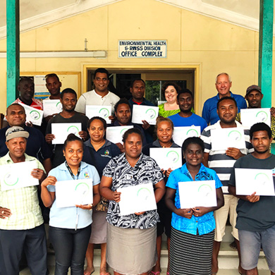 Five Solomon Islander women, twelve Solomon Islander men, an Australian woman and an American man stand on a set of stairs in front of a yellow and green building. The fifteen training participants are holding certificates and are smiling at the camera.