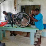 Three Ni-Vanuatu men are assembling a wheelchair, on top of a blue, wooden table.