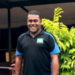 Jope stands outside of Frank Hilton Organisation smiling at the camera. He is wearing a black and blue uniform work shirt and a traditional Fijian mens sulu vakatoga. There is a lush green garden in the background.
