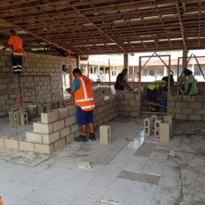 A building site, with half of the tiles removed on the floor, and new brick walls being laid by bricklayers in high-vis vests.