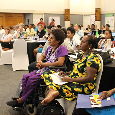 Conference delegates listening to a presenter off screen. In the fore ground are two women in colourful dresses.