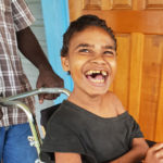 Joseph sits in his new wheelchair smiling brightly.