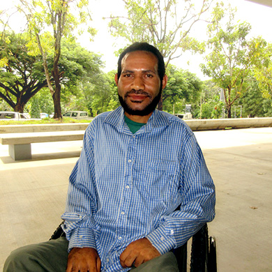 Peterson is sitting in his wheelchair outside the Business building at the University of PNG. He is in a blue and white striped shirt, behind him, we see concrete benches and trees.