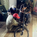 Samuel, sitting in his wheelchair with a tricycle attachment. Sammy and Alfred are adjusting his footplates to improve the angle.