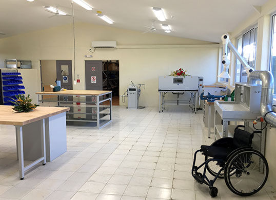 Photo of the workshop newly renovated ready for the opening. Work benches and prosthetic machinery such as ovens and fume extractors are in view. A wheelchair is displayed.