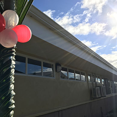 A photo of the outside of the building, with a decorated post in the foreground. It is wrapped with palm fronds and tied with balloons for the opening ceremony.
