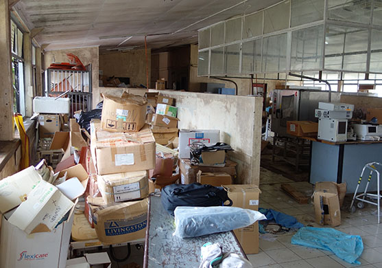 A photo of the derelict building before we began renovations. You can see boxes stacked high, tables with electronic equipment on them.