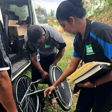 A photo of Nisha and two other man of the Frank Hilton Organisation taking wheelchair parts out of a van.