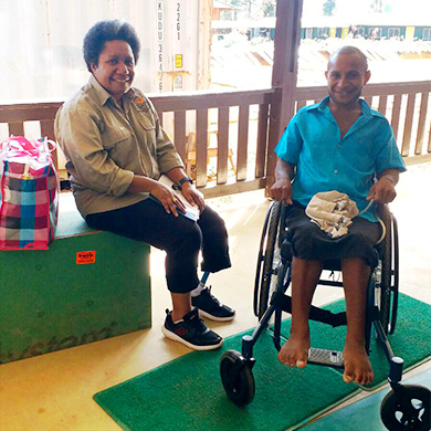 John and Almah Sit on the veranda of the Kompiam Hospital. John is smiling as he sits in his new wheelchair.