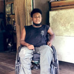 A young man from the Solomon Islands sits in his new wheelchair and smiles at the camera.