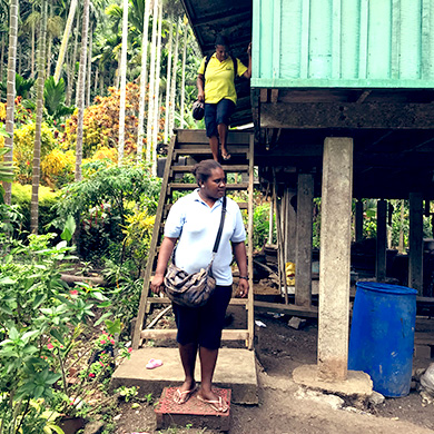 A woman from the Solomon Islands in a bright yellow t'shirt walks down a steep set of stairs from a wooden house on stilts whilst another woman in blue waits at the bottom. The house is surrounded by tropical vegetation.