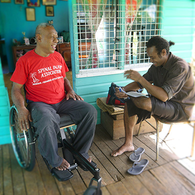Two men smile and laugh with each other. The man on the left is using a wheelchair, the man on the right in seated with a document in front of him. They are on the porch of a home.
