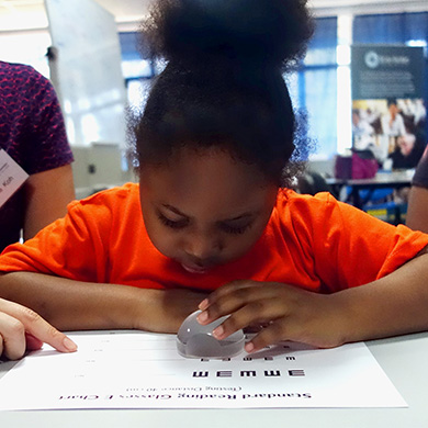 A young girl uses a dome magnifier to read letters on a paper on a table in front of her.