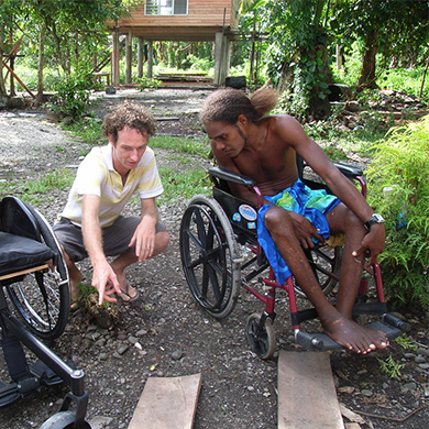 A young man crouches beside another man using a wheelchair. They are looking at another wheelchair.